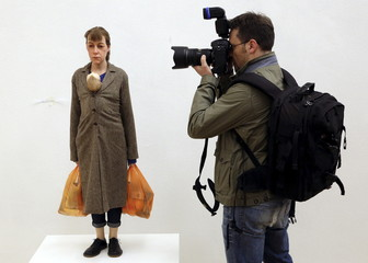 "A photographer takes a picture of ""Woman with shopping"" by Ron Mueck during the unveiling of the Arts & Food exhibition at the Triennale as part of the upcoming Expo 2015 in downtown Milan"