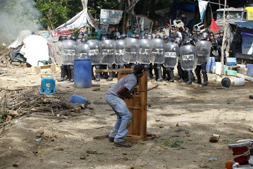 Opponent of Tambor mining project takes shelter behind a table in front of a line of riot police evicting protesters against project in San Jose del Golfo