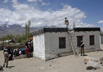 A security officer climbs on the roof of a polling station in Ladakh