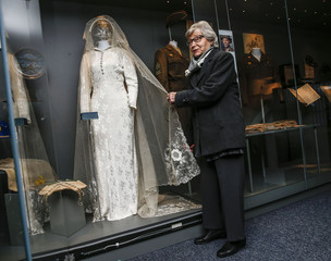 GI bride Peggy Albertson, who married American airman Joe Albertson poses for a picture with her wedding dress at The American Air Museum