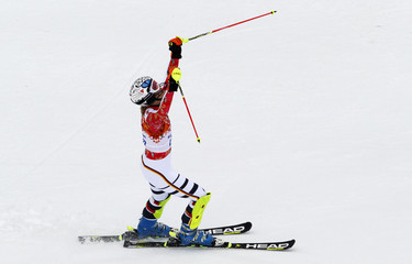Germany's Hoefl-Riesch raises her ski poles after finishing first in her slalom run of the women's alpine skiing super combined event at the 2014 Sochi Winter Olympics