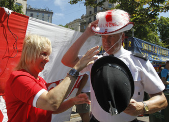 A British police officer excahanges his helmet with the hat of a supporter of England at the fan zone in Kiev