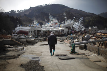 A man walks next to port area destroyed by the earthquake and tsunami in Kessenuma town
