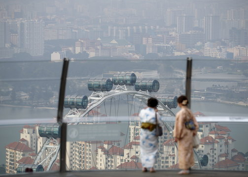 Women wearing kimonos look at the Singapore Flyer shrouded by haze near the central business district in Singapore