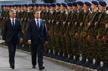 Swiss President Burkhalter and Luxembourg's Prime Minister Bettel walk past the guard of honour in Neuenburg