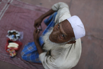 A Muslim man sits before iftar meal on the first day of Ramadan in India at Jama Masjid in Delhi