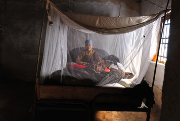 A Taoist hermit priest sits on her bed during her daily meditation in Mount Zhongnan