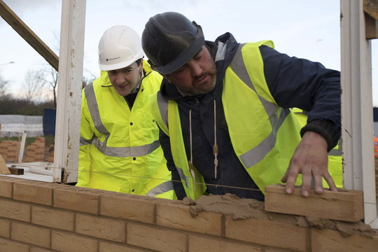 Britain's Chancellor of the Exchequer George Osborne is shown how to lay a brick during a visit to a housing development in South Ockendon in Essex, Britain