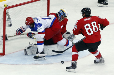 Switzerland's goalkeeper Genoni and Romy save in front of Russia's Tikhonov during the third period of their men's ice hockey World Championship Group B game at Minsk Arena in Minsk