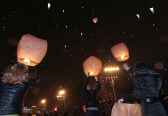 People release sky lanterns under a snowfall as they take part in a flash mob in central Krasnoyarsk in Siberia