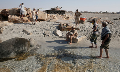 Fighters of Libyan forces allied with the U.N.-backed rest on a beach before they fire a shell with Soviet made T-55 tank at Islamic State fighters from a beach in Sirte