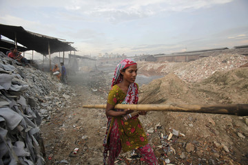 A woman carries a bamboo stick in a tannery while working at Hazaribagh in Dhaka