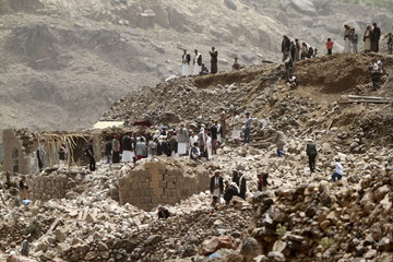 People stand on the rubble of houses destroyed by an air strike in Okash village near Sanaa