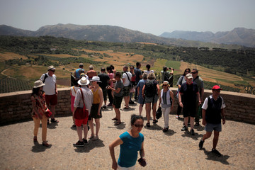 Tourists stand on a balcony as they look at the landscape in Ronda