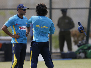 The hat of Sri Lanka's Malinga flies off due to wind while he speaks to team's batting coach Atapattu during a practice session ahead of their final One Day International cricket match against South Africa, in Hambantota