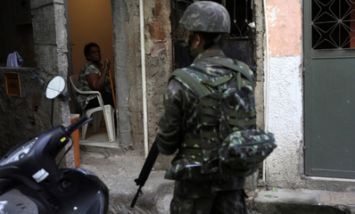 A resident looks on as a Brazilian Army soldier patrols the Mare slums complex in Rio de Janeiro