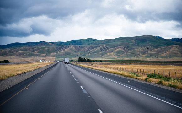 Scenic road with caravans semi trucks and undulating hills