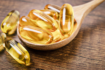 Fish oil capsules with omega 3 and vitamin D in a wooden spoon.