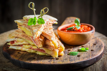 Spicy quesadilla made of tortilla with cheese and ham