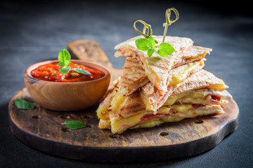 Spicy quesadilla made of tortilla with sauce and herbs