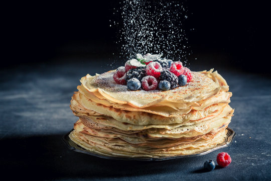Delicious stack of pancakes with fresh berries and mint