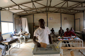 A voter casts his ballot at a polling station during the country's presidential and legislative elections in Niamey
