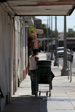 A man pulls a trolley past a row of closed businesses on Main Street in Stockton, California