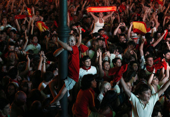 Spanish fans celebrate Spain's goal as they watch the 2010 World Cup final soccer match between Spain and the Netherlands on an outdoor TV screen during the San Fermin festival in Pamplona