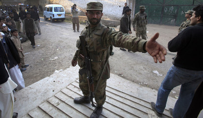 A soldier secures the area near the site of a bomb blast in Peshawar
