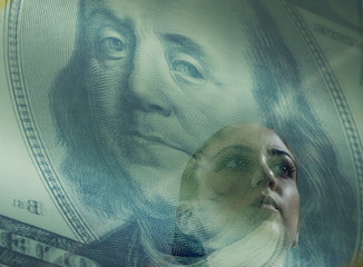 A woman passes by a reflection of a poster of a Benjamin Franklin 100 dollar bill at a money changer in Singapore