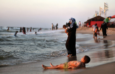 Palestinians enjoy the warm weather at a beach in Gaza City