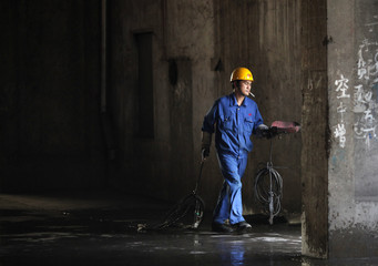 A steel worker carries tools at the Huaxi Iron and Steel Company plant in Huaxi village