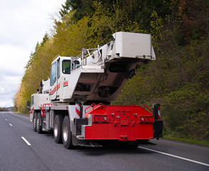 Large wheeled mobile portable crane with extendable boom on road