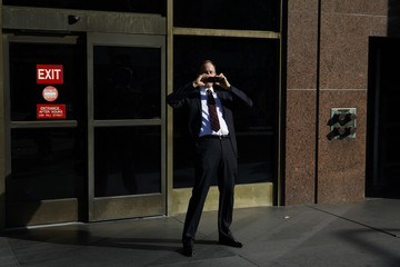A man takes pictures of the media gathered outside the Los Angeles County Superior Court for the first day of a civil trial against AEG Live in Los Angeles