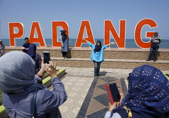 Visitors to the coastline take pictures with the Indian Ocean in the background a day after a 7.8 magnitude earthquake struck far out at sea in Padang, West Sumatra province, Indonesia