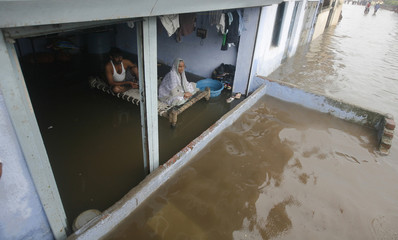 Residents sit inside their flooded house after heavy rains in Ahmedabad