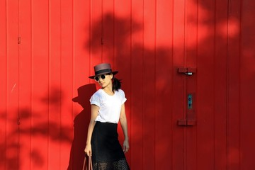 Fashion style portrait of young trendy girl with brown hat. Model posing and standing near red wall.