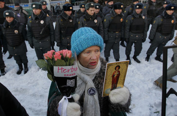 Woman holds an icon and flowers in front of a line of police during an unauthorised rally in central Moscow