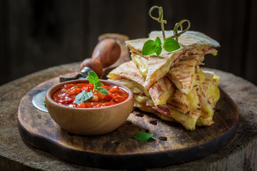 Spicy tortilla as quesadilla with sauce and herbs