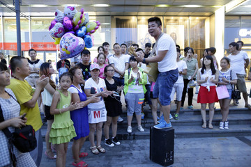 Street musician Zhang Mingyuan sings on a sound box during his daily performance at a square outside a shopping mall in Beijing