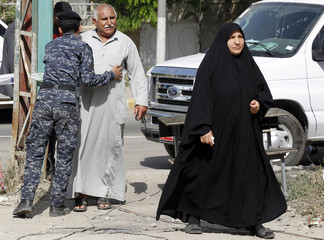 Policeman frisks a resident outside a polling station in Baghdad