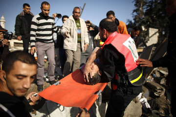Members of the Palestinian Civil Defense carry a survivor after he was pulled out from the rubble of his destroyed house after an Israeli air strike in Gaza City