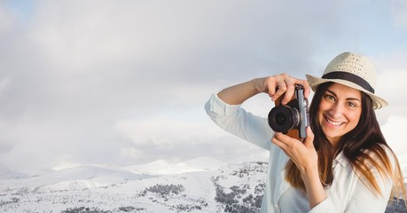 Hipster clicking photographs by snowcapped mountains against sky