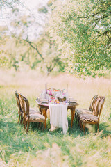 The beautiful view of the wedding table setting places in the green sunny field. The old-fashion chairs.