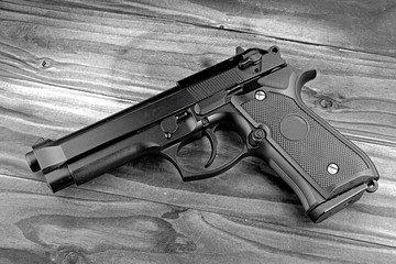 Weapon series. Modern U.S. Army handgun M9 close-up on grey wooden background. (Black & White)