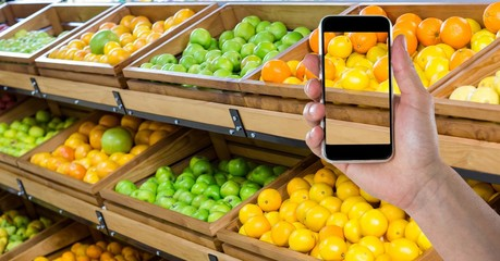 Hand taking picture of fruits with smart phone in grocery shop