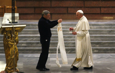 Pope Francis receives a stole that had belonged to Don Diana, who was killed by the mafia, from Father Luigi Ciotti during an audience with the family members of victims of the mafia, in Rome