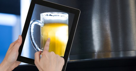 Hand taking picture of beer glass through digital tablet