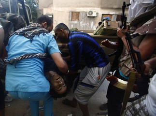 A medic and Libyan rebel fighter carry the body of a comrade during a fight for the final push to flush out Muammar Gaddafi's forces in Abu Salim district in Tripoli