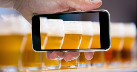 Hand taking picture of beer glasses through smart phone at bar